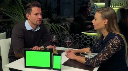 A man and a woman (both young and attractive) sit at a table in a restaurant and talk, a tablet and a smartphone (both green screens) sit on a table, closer to the camera