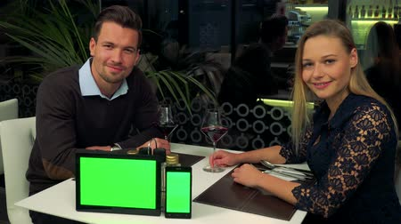 A man and a woman (both young and attractive) sit at a table in a restaurant and smile into the camera, a tablet and a smartphone with green screens on a table