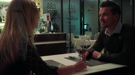 A young, handsome man and a woman sit at a table in a restaurant, talk, then clink glasses of wine and drink Stock Footage