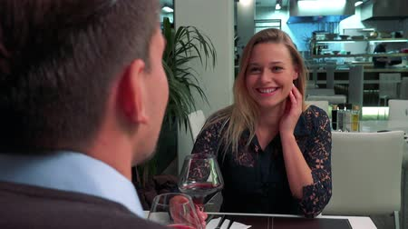 A man (the back of his head to the camera) and a young, beautiful woman sit at a table in a restaurant, drink wine and talk
