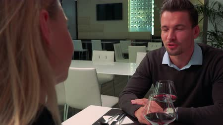 A woman and a young, handsome man sit at a table in a restaurant, drink wine and talk