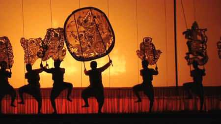 stín : Actors perform big Puppet on stage.Light from bonfire through front cloth screen show color,pattern and texture.Actors rhythmically dance with old style Thai song.Theme show is Narayana story.