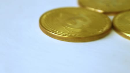 снижение : three gold coins bitcoins, spinning on white background