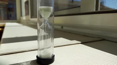 áttekinthetőség : hourglass with a fleeting white sand inside, stand on a window sill, time lapse Stock mozgókép
