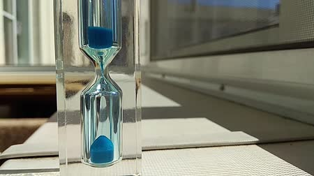 áttekinthetőség : hourglass with a quick-flowing blue sand inside, stand on the windowsill, time lapse Stock mozgókép