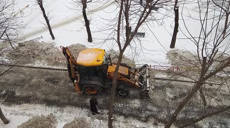 buldózer : yellow tractor cleans the road from the snow in a residential area of the city