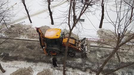 муниципальный : yellow tractor cleans the road from the snow in a residential area of the city