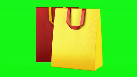купить : two red and yellow shopping bags loop rotate on green chromakey background