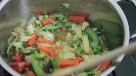 kavurma : steaming vegetables like pea, carrots, cauliflower, mung bean sprouts, mushroom, young bamboo sprouts in cooking pot with wooden spoon