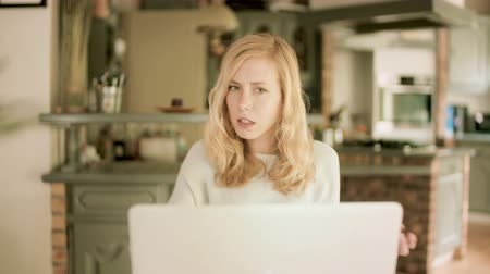 Young blond woman sitting at a table at home looking at her laptop
