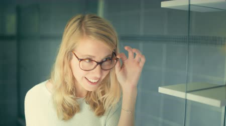 女性たち : Slow motion of young blond caucasian woman walking in the bathroom, looking at glasses and looking at herself in the mirror, happy and satisfied, enjoying her reflection 動画素材