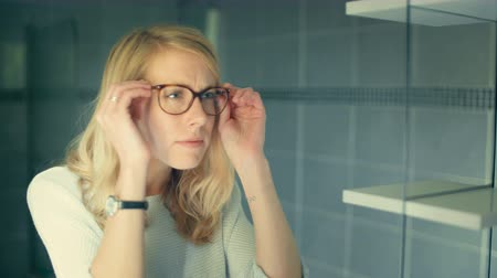 szemüveg : Slow motion of young blond woman in the bathroom, looking at glasses and looking at herself in the mirror, not very happy, disgusted by her reflection
