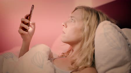 sekély : Woman lying in bed looking at her smartphone suddenly shocked by what she is looking at - slow motion