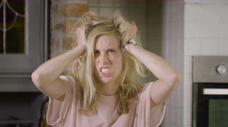 irritação : Beautiful blond woman going crazy messing up her hair looking at the camera