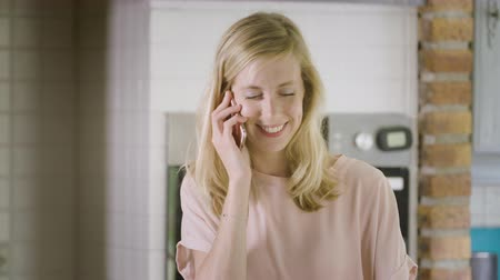 Close up of woman in kitchen making a call and making a call with her smartphone smiling Стоковые видеозаписи