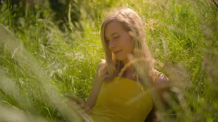 Peaceful young blond caucasian woman sitting in the garden outdoors using Smart Phone. 4K slow motion Стоковые видеозаписи