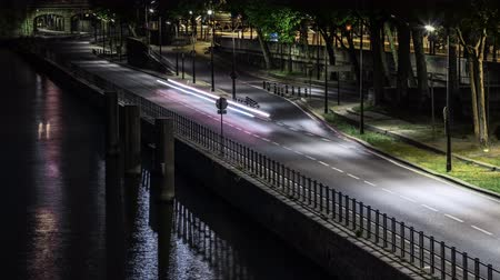 Time Lapse of an urban road junction in Paris France at night with fast motion in the river
