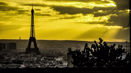 Time lapse of a tower of the Eiffel tower and the city of Paris in the background of a yellow sky and the sun, beautiful rays of light Стоковые видеозаписи