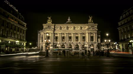 Time lapse of the illuminated famous landmark Opera Garnier at night time, with its busy street full of cars and crowds. Paris, France.