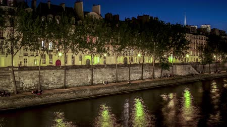 Time lapse of the Quai de Seine in Paris France at night with a wall, beautiful architecture and trees on the boarder of the water with reflections of the lights and boats passing by