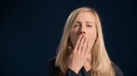 Slow motion portrait of a caucasian woman with blond hair yawning with her hand over her mouth
