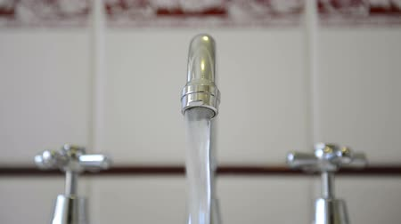 mosogató : Water running out of a chrome tap faucet with tiles behind Stock mozgókép