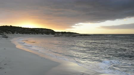 beach panorama : Waves gently lapping the sandy shore at sunset with dramatic clouds