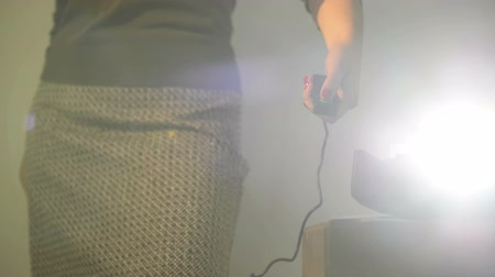 slayt : Retro styled footage of a woman operating a slide projector with a wired remote control and lens flare from projector light