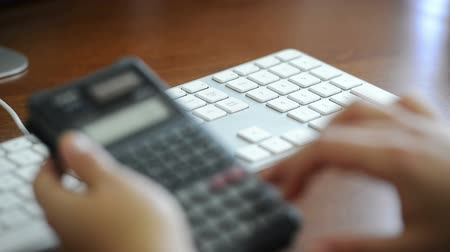 impostos : An accountant enters expenses on a calculator and into the computer keyboard for tax records Stock Footage