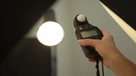 lighting equipment : Person in photography studio using studio flash lighting equipment to photograph Stock Footage