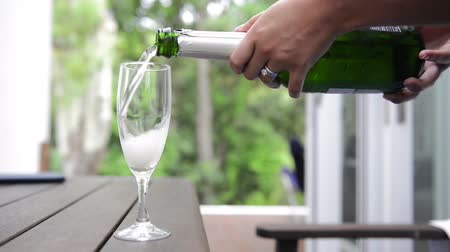 szampan : Woman pours bubbly champagne into a champagne flute glass on outdoor table Wideo
