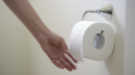 sanitário : Person unrolls toilet paper tissue in the toilet