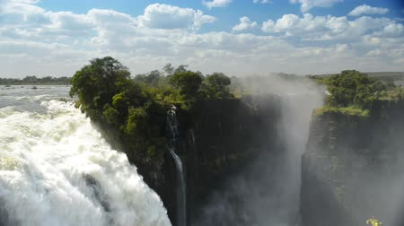 zambia : Victoria Falls Devils Cataract or Mosi-oa-Tunya waterfall in southern Africa on the Zambezi River at the border of Zambia and Zimbabwe in high definition footage. Victoria Falls is one of the 7 Wonders of the Natural World. Panning shot with ambient audio Stock Footage