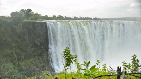 zambia : Victoria Falls or Mosi-oa-Tunya flowing waterfall in southern Africa on the Zambezi River at the border of Zambia and Zimbabwe in high definition panning footage with ambient audio. Victoria Falls is one of the 7 Wonders of the Natural World.
