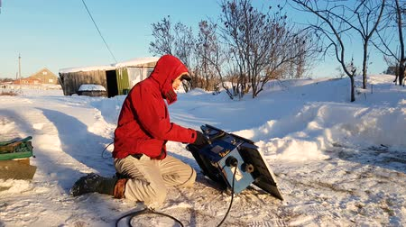 separado : Young man repairing, circular saw, winter on the street, in the countryside Vídeos