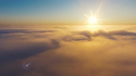 questão : Aerial View. Flying in fog, fly in mist. Aerial camera shot. Flight above the clouds towards the sun. Misty weather, view from above.