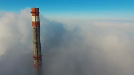 Aerial View. Flying in fog, fly in mist. Aerial camera shot. Flight above the clouds towards the sun. Misty weather, view from above.