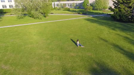 Aerial view. Young girl lying and resting on lawn on sunny day in park on grass. Above view. Woman on grass in meadow. Top view Vídeos