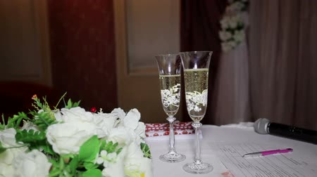 элегантный : Two glasses with champagne and wedding bouquet on the table Стоковые видеозаписи