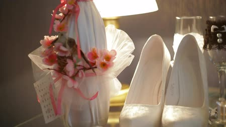 marfim : Beautiful white bridal shoes and a bottle of champagne on the table