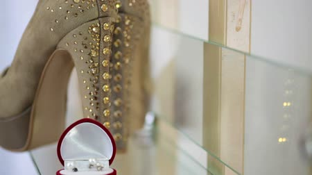 cerimônia : golden wedding rings in a box and bridal shoes on the table