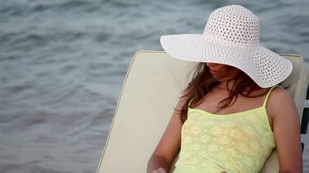 supermodel : beautiful woman in a hat and sunglasses sunbathing on the beach on a lounger