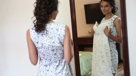 denemek : Bride trying on wedding dress before the mirror