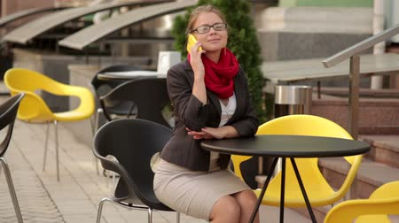 estilo de vida : business and lifestyle concept - smiling young woman in eyeglasses calling on smartphone at cafe