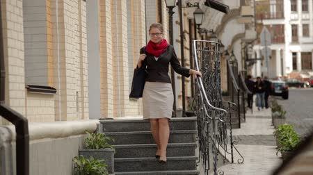 escada : Elegant young woman in glasses walking on stone stairs Stock Footage