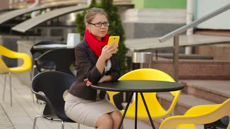 proprietário : businesswoman at a table in a cafe looking into a smartphone