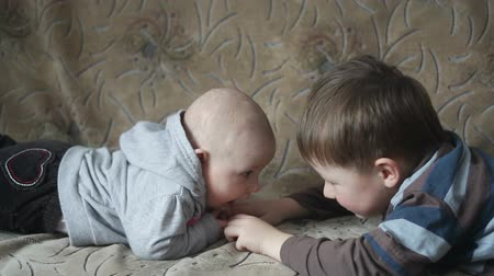 сестра : Little brother and sister lying on the couch facing each other