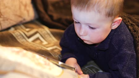 использование : little boy watching cartoon on a smartphone indoor