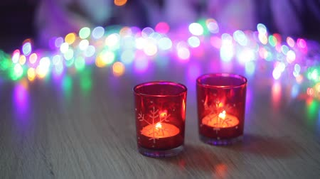 embellished : two red candlestick and multi-colored lights in the background Stock Footage