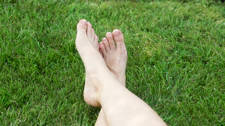 outside view : Female legs on the green grass in the park
